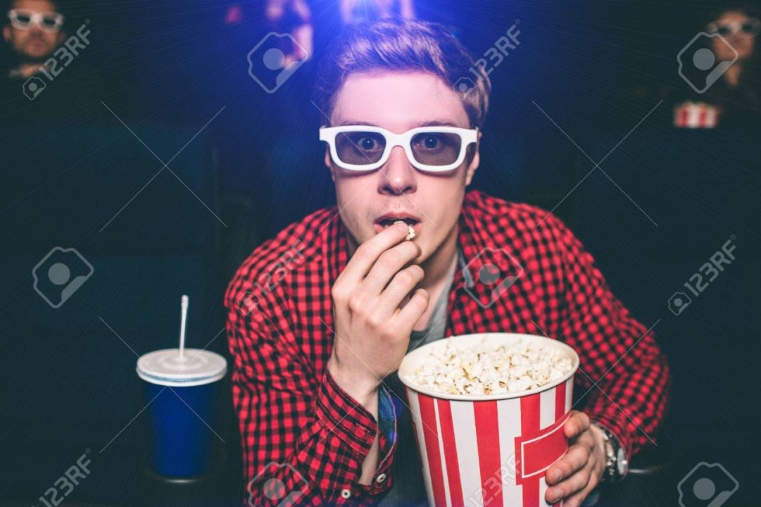 101349955-a-portrait-of-guy-sitting-in-chair-in-cinema-hall-and-eating-popcorn-he-is-looking-straight-very-int.jpg